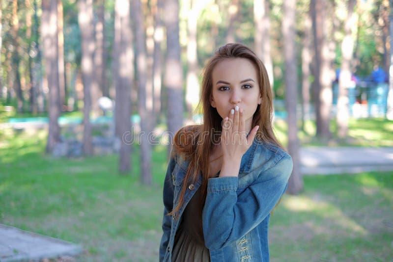 Härlig ung kvinna som blåser en kyss som är utomhus- royaltyfri fotografi