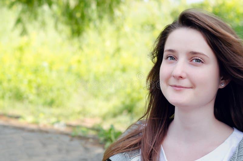 Härlig ung kvinna som dagdrömmer i en parkera fotografering för bildbyråer