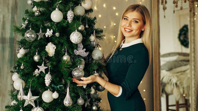 Härlig ung kvinna som dekorerar en julgran arkivbild