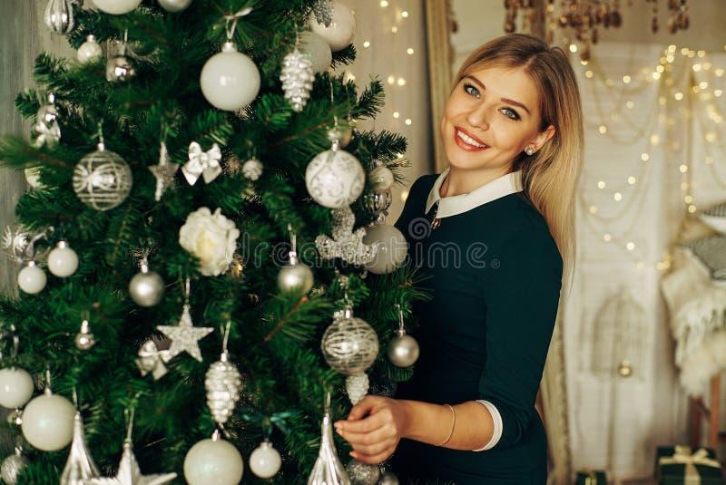 Härlig ung kvinna som dekorerar en julgran royaltyfri fotografi