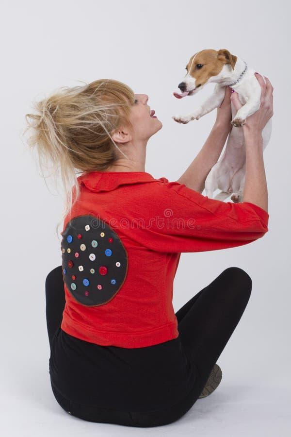 Härlig ung kvinna som delar förälskelse med den stålarrussell hunden, medan de spelar royaltyfri bild