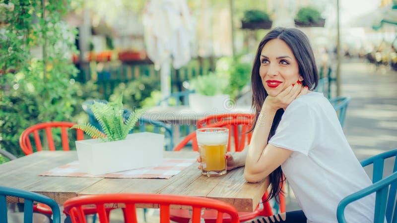 Härlig ung kvinna som dricker öl och tycker om sommardag arkivbilder