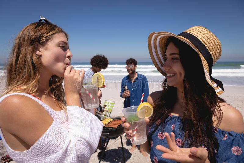 Härlig ung kvinna som dricker coctailexponeringsglas på stranden i solskenet royaltyfria bilder