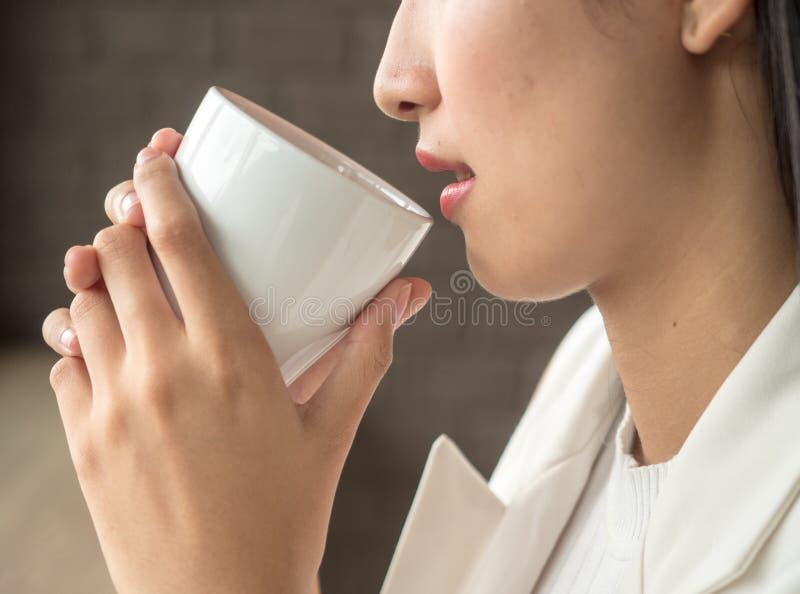 Härlig ung kvinna som dricker kaffe i morgonen, kvinnliga händer för närbild som rymmer en kopp av cappuccino arkivfoto
