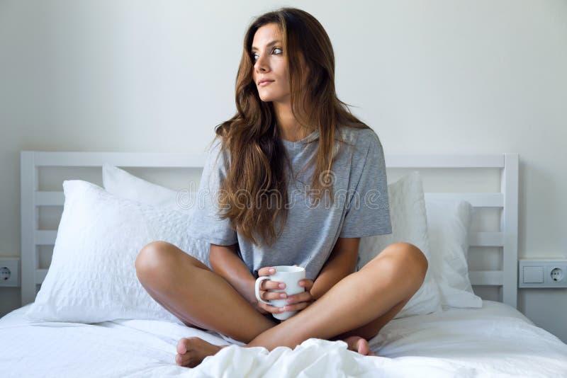 Härlig ung kvinna som dricker kaffe i sängen arkivfoto