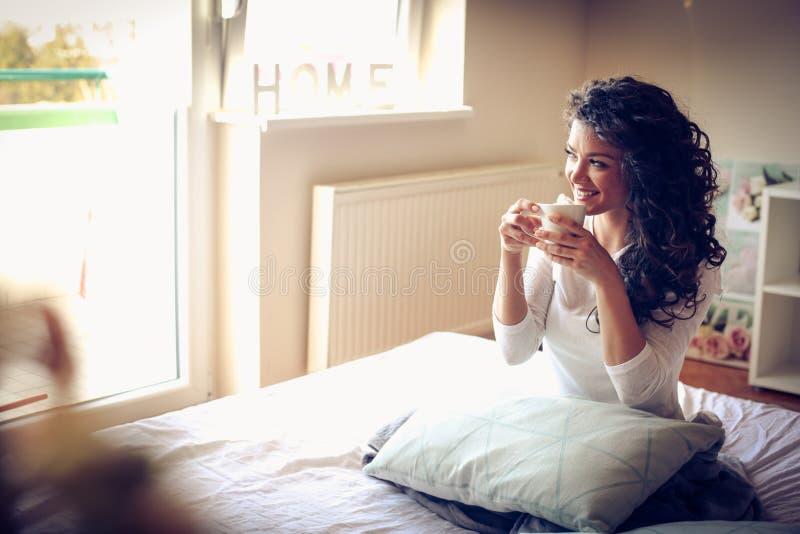 Härlig ung kvinna som dricker morgonkaffe i säng A arkivfoton