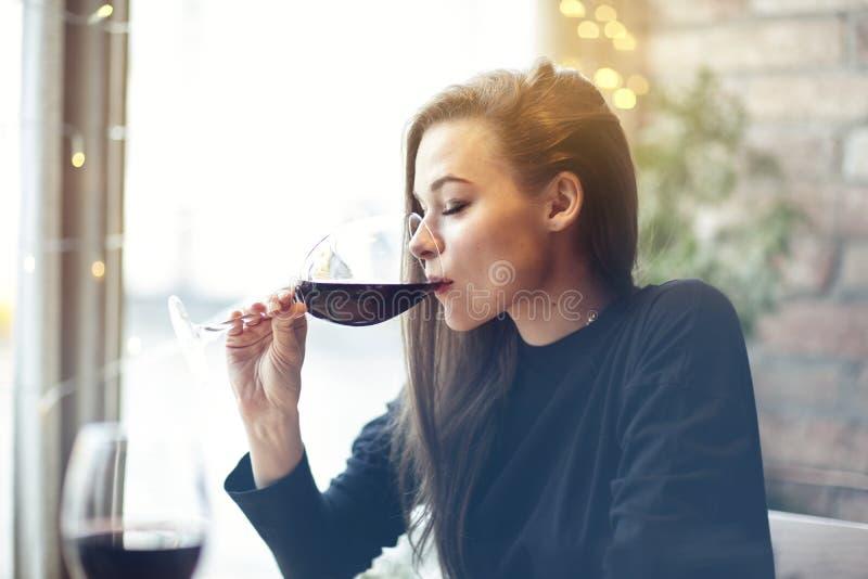 Härlig ung kvinna som dricker rött vin med vänner i kafét, stående med vinexponeringsglas nära fönster Kall semestrar den conc af royaltyfri foto