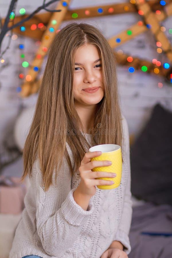 Härlig ung kvinna som dricker te på julgranen royaltyfria foton