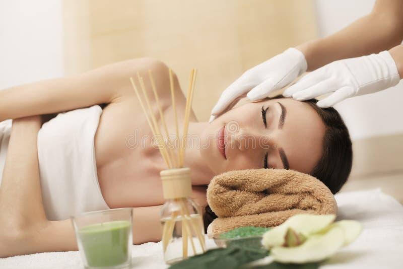 Härlig ung kvinna som får den ansikts- massagen som ligger på soffan arkivfoton