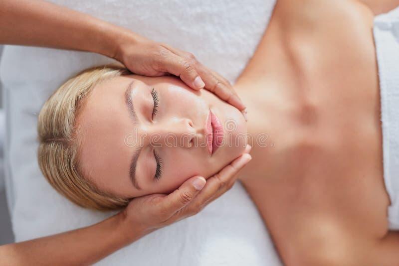 Härlig ung kvinna som får en ansikts- massage royaltyfri fotografi
