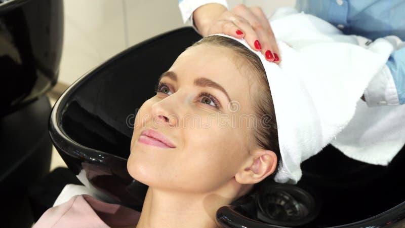 Härlig ung kvinna som får hennes våta hår slåget in i en handduk av en yrkesmässig frisör royaltyfria foton