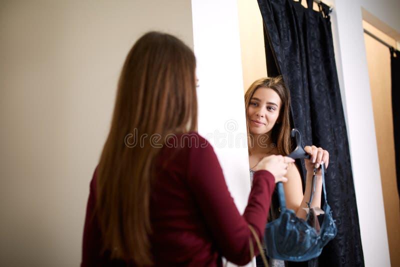 Härlig ung kvinna som frågar för en vänåsikt i provhytten av damunderkläderlagret Kvinnlign försöker på behån in royaltyfri bild