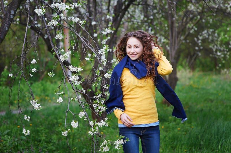 Härlig ung kvinna som går i en blomstra vårträdgård royaltyfri fotografi