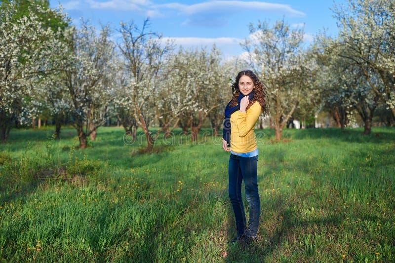 Härlig ung kvinna som går i en blomstra vårträdgård royaltyfria foton