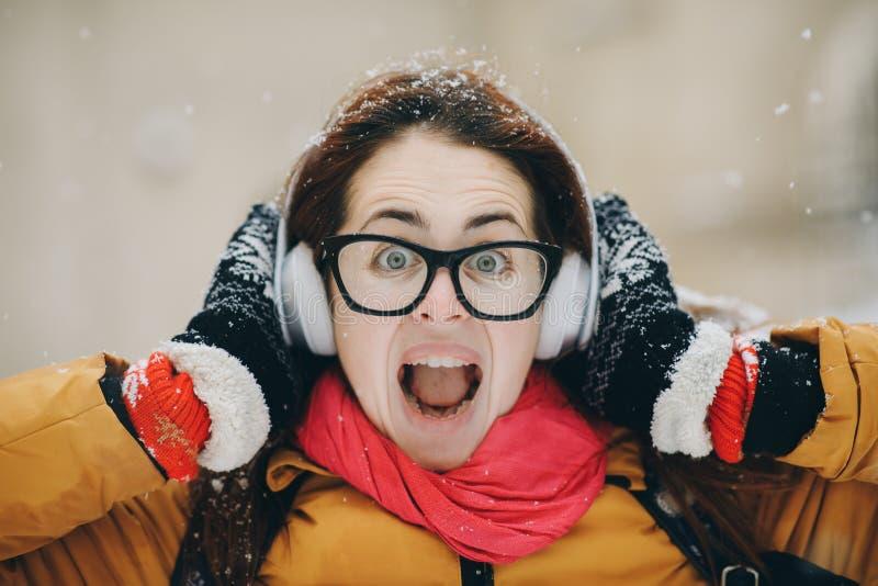 Härlig ung kvinna som går i vinterskog och lyssnar till musik Livsstil vintermode, skönhet fotografering för bildbyråer