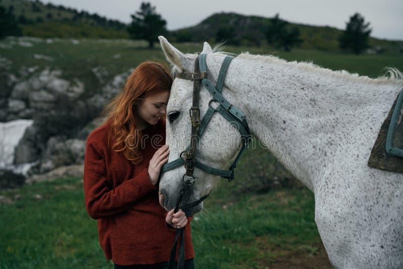 Härlig ung kvinna som går med en vit häst i bergen, natur arkivbilder