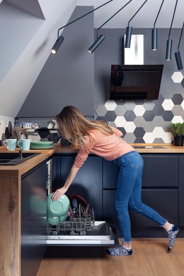 Härlig ung kvinna som gör disk i köket royaltyfria bilder