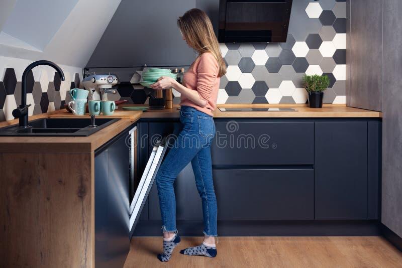 Härlig ung kvinna som gör disk i köket royaltyfri bild