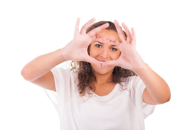 Härlig ung kvinna som gör en hjärta med händer arkivfoton