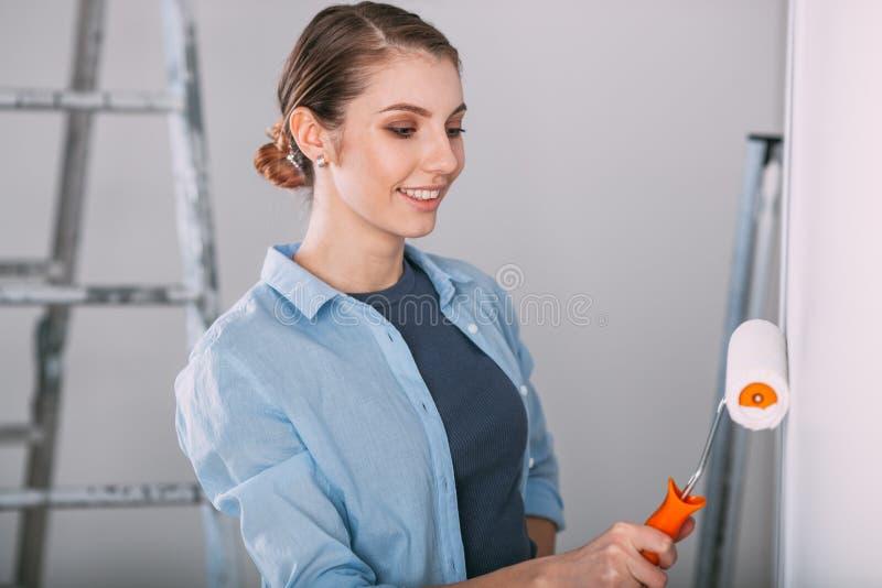 Härlig ung kvinna som gör väggmålning royaltyfri foto