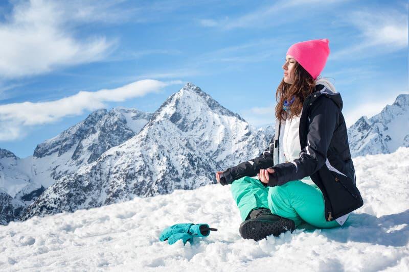 Härlig ung kvinna som gör yoga i snöbergen royaltyfri fotografi