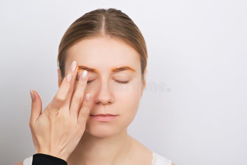 Härlig ung kvinna som har ögonbrynkorrigeringstillvägagångssätt arkivbilder