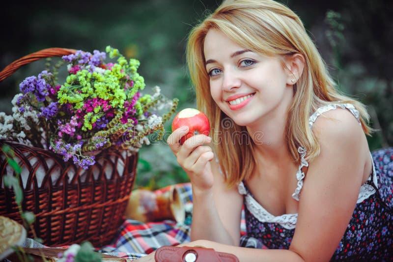 Härlig ung kvinna som har en picknick i bygden Lycklig hemtrevlig dag utomhus öppet Le kvinnan som äter äpplet som kopplar av i t royaltyfria foton