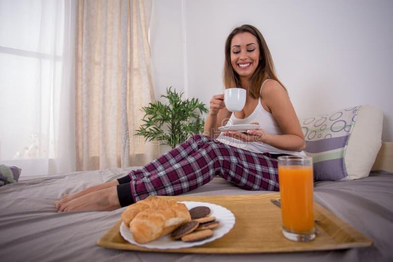 Härlig ung kvinna som har frukosten i säng arkivfoton