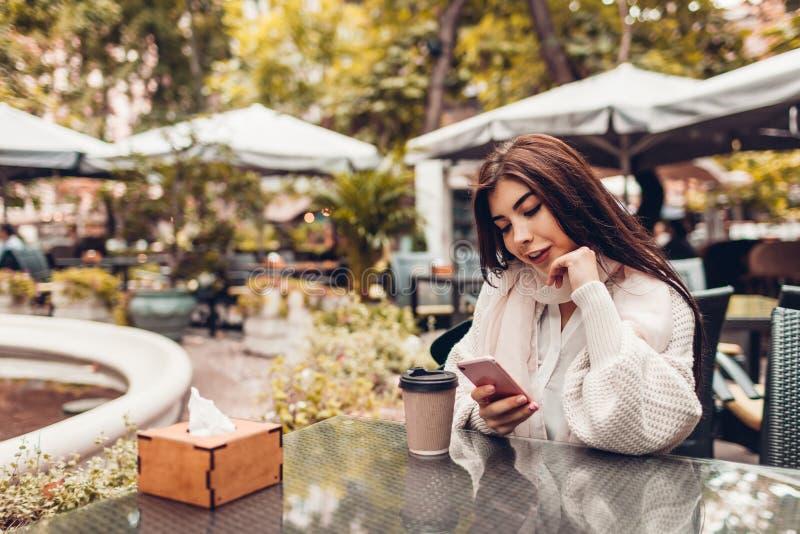 Härlig ung kvinna som har kaffe i utomhus- kafé, medan genom att använda smartphonen Stående av det stilfulla flickamaskinskrivni royaltyfria foton