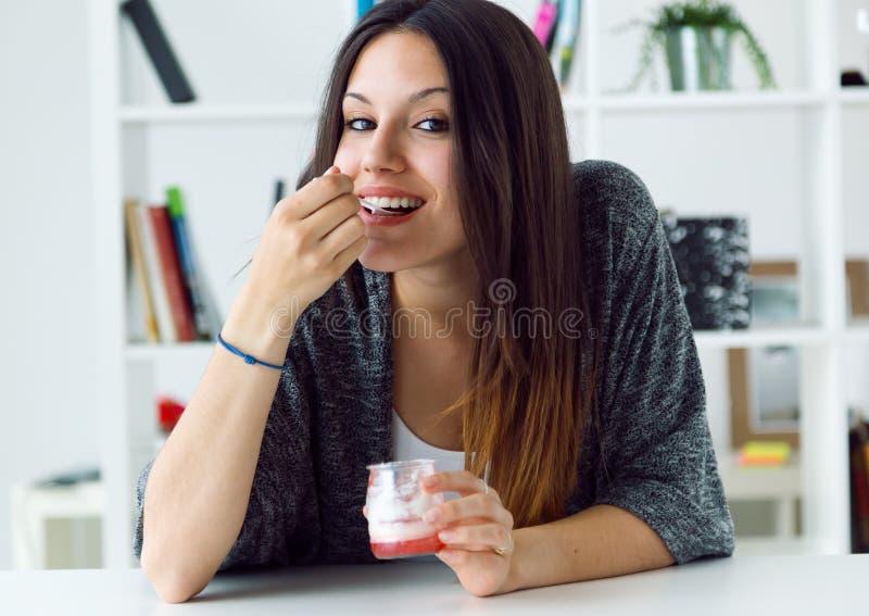 Härlig ung kvinna som hemma äter yoghurt arkivbild