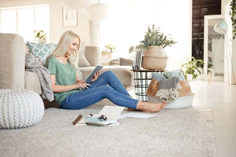 Härlig ung kvinna som hemma använder den digitala minnestavlan royaltyfria foton