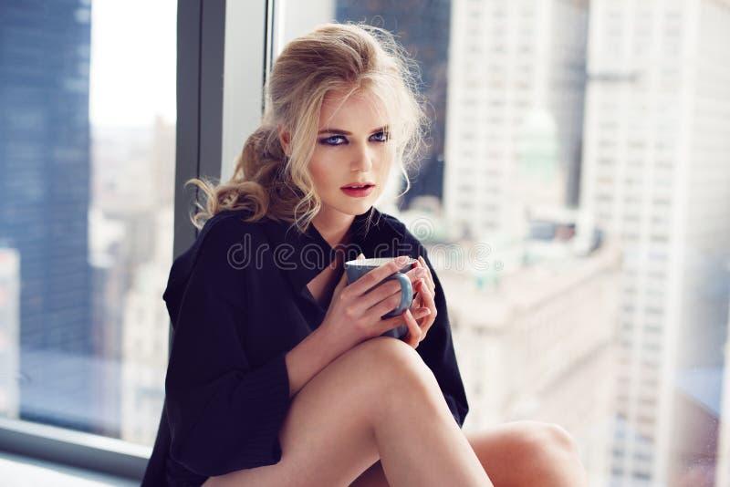 Härlig ung kvinna som hemma dricker kaffe på morgonsammanträdet vid fönstret royaltyfria foton