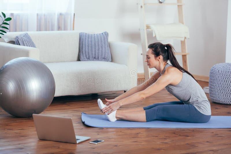 Härlig ung kvinna som hemma gör yoga arkivbild