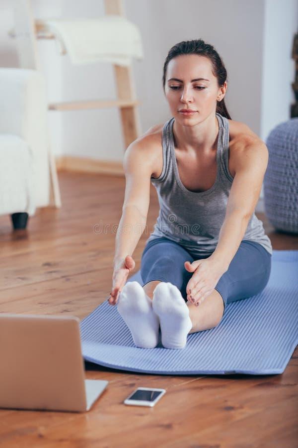 Härlig ung kvinna som hemma gör yoga arkivfoto