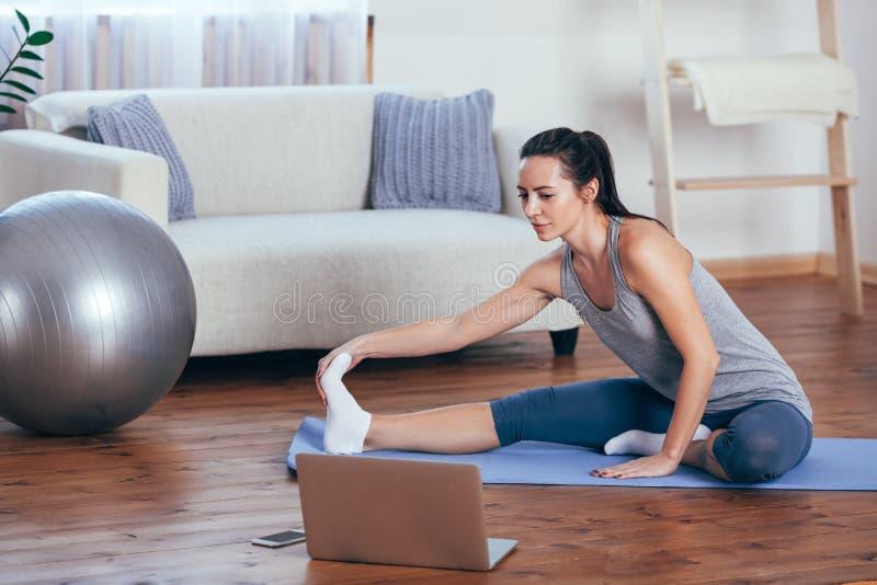 Härlig ung kvinna som hemma gör yoga fotografering för bildbyråer
