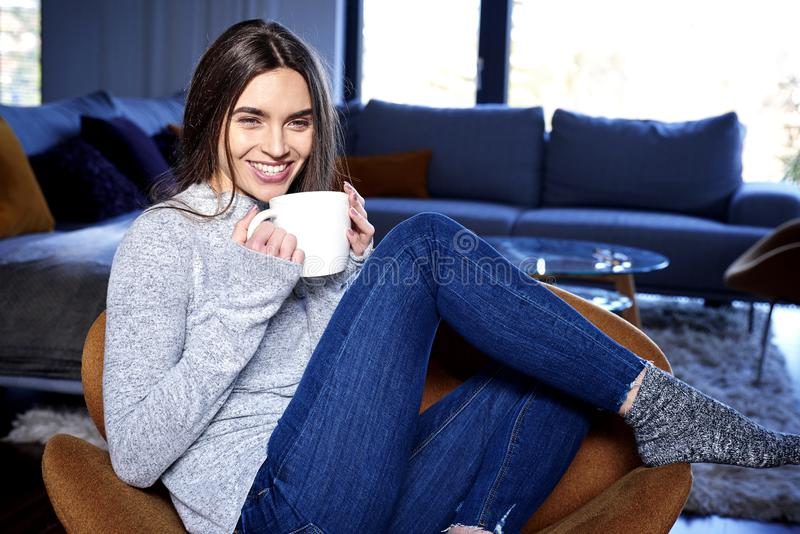 Härlig ung kvinna som hemma kopplar av och har en kopp te royaltyfri bild