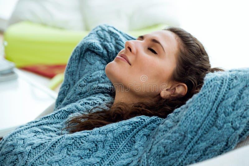 Härlig ung kvinna som hemma kopplar av på soffan royaltyfria bilder