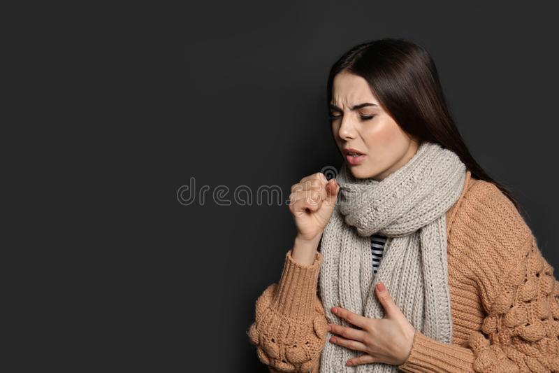 Härlig ung kvinna som hostar mot mörker Utrymme för text royaltyfri foto