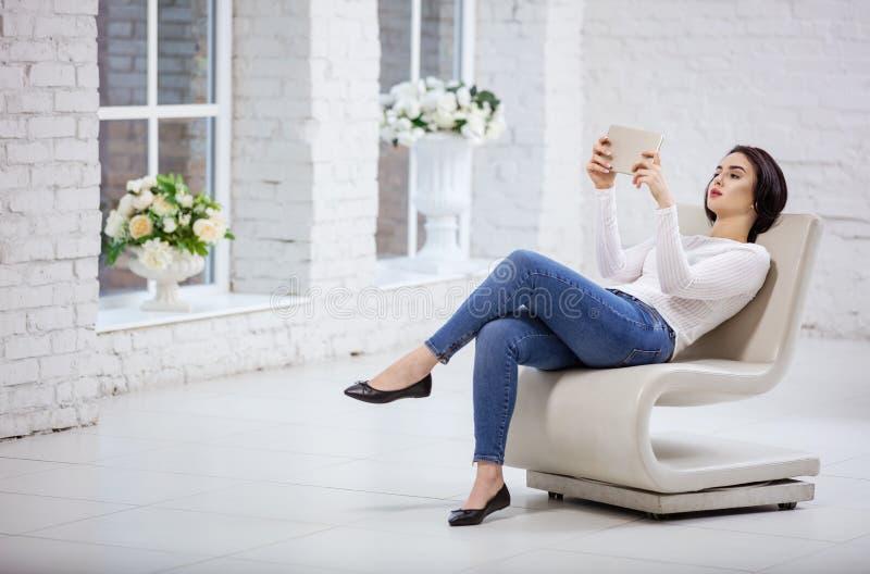 Härlig ung kvinna som inomhus använder minnestavlan arkivfoton