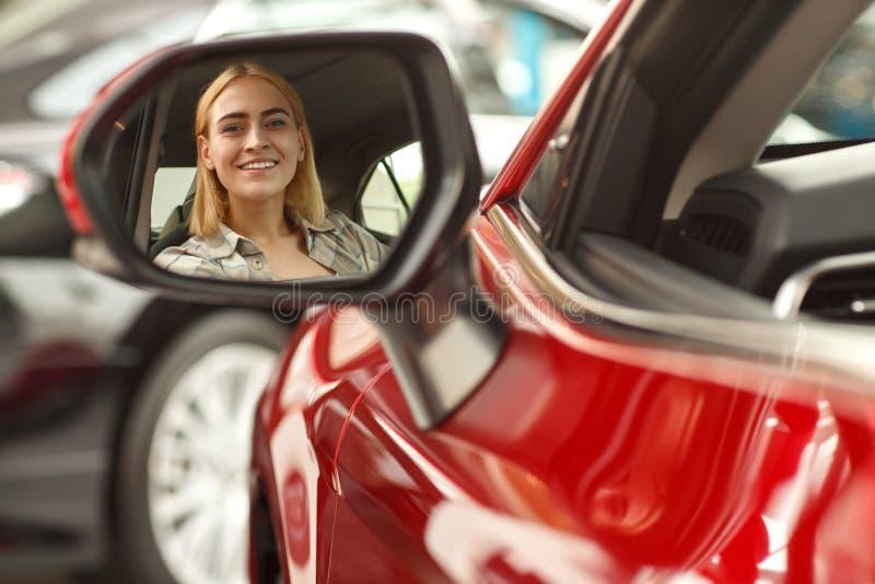 Härlig ung kvinna som köper den nya bilen på återförsäljaren royaltyfri fotografi