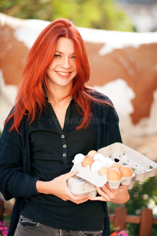 Härlig ung kvinna som köper nya ägg på en lantgård arkivfoton