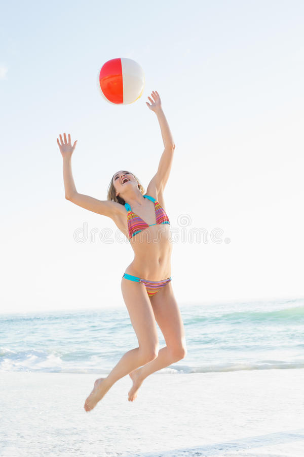 Härlig ung kvinna som kastar en strandboll royaltyfria foton