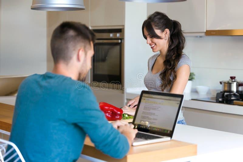 Härlig ung kvinna som klipper grönsaker på en trätabell medan hennes make som hemma använder bärbara datorn i köket royaltyfri foto