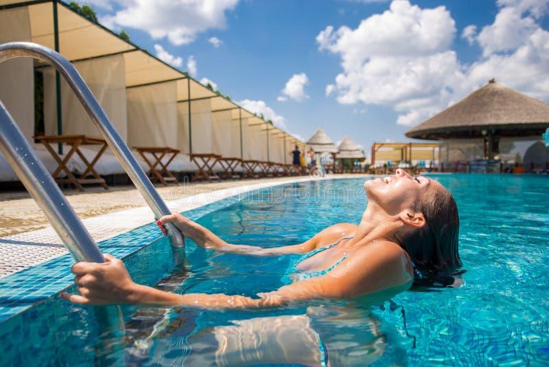 Härlig ung kvinna som kliver ut ur en simbassäng royaltyfria bilder