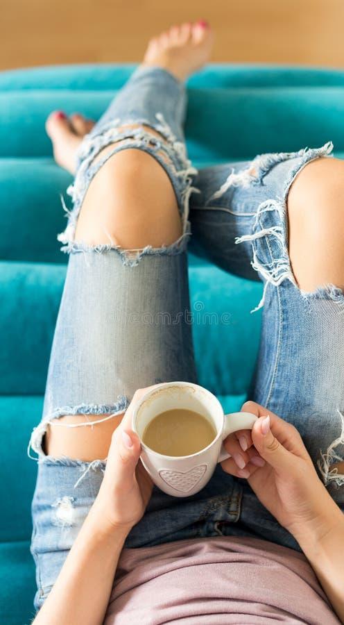 Härlig ung kvinna som kopplar av på den hemmastadda hållande ögonen på tv:n för soffa och tycker om kaffe, bästa sikt royaltyfria bilder