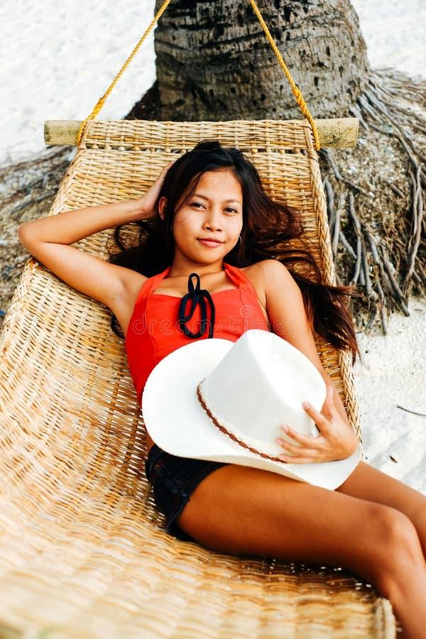 Härlig ung kvinna som kopplar av på rottinghängmattan på den vita sandstranden under loppsemester royaltyfri foto