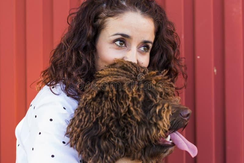 Härlig ung kvinna som kramar hennes hund, en brun spansk vattenhund royaltyfri foto