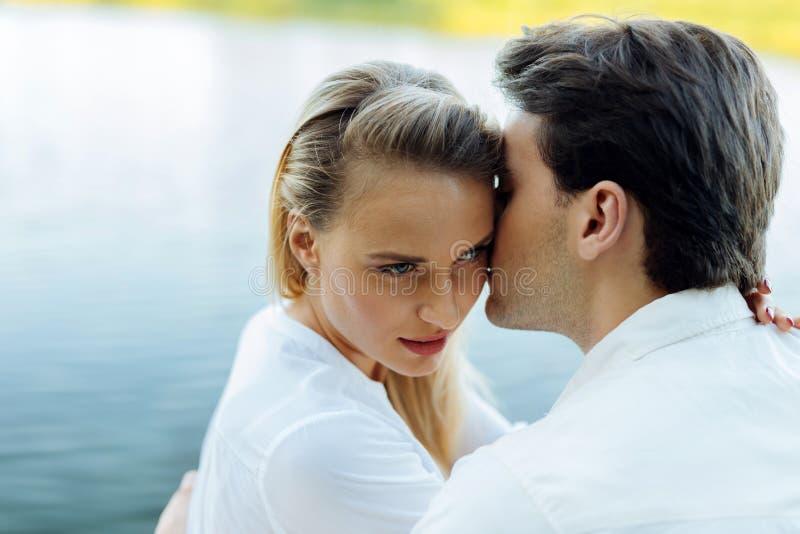 Härlig ung kvinna som kyssas av hennes make royaltyfri fotografi