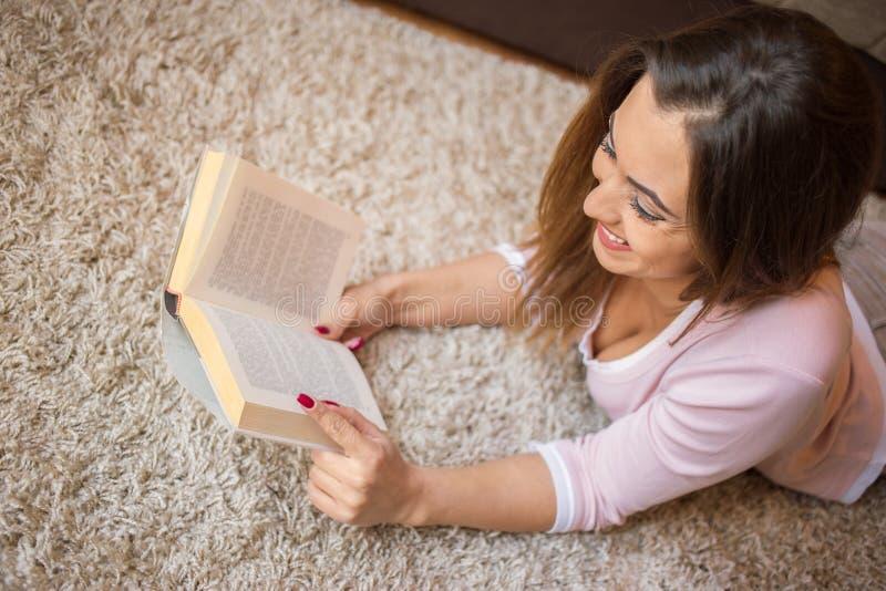Härlig ung kvinna som läser en bok på golvet royaltyfri fotografi
