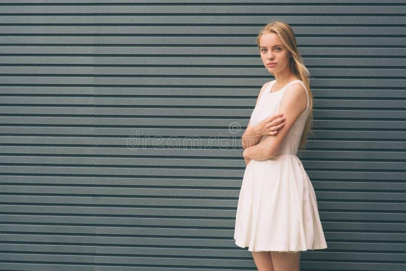 Härlig ung kvinna som ler och står med korsade armar mot den gråa väggen arkivbild